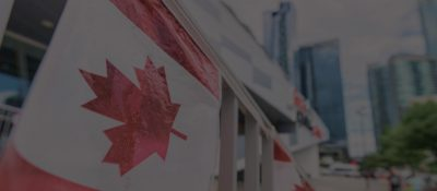 anada plastic flag with blurred urban background in Toronto